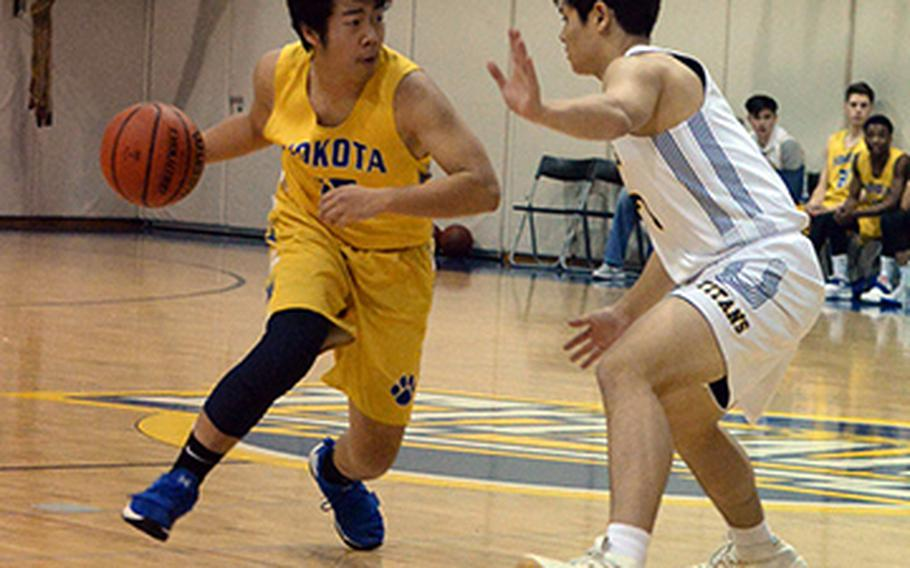 Yokota's Ken Baarde dribbles against St. Mary's Ricky Story during Friday's Japan boys basketball game, won by the Panthers 52-32.