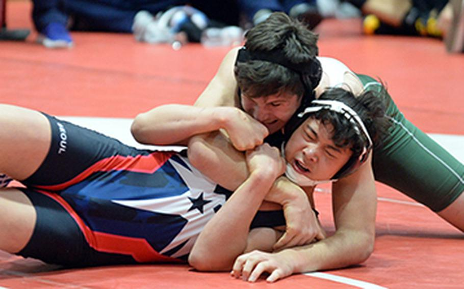 """Kubasaki's Nick Burwell gets the edge on Seoul American's Brian Choe in the 180-pound final during Saturday's 25th Nile C. Kinnick Invitational """"Beast of the Far East"""" Wrestling Tournament. Burwell won by technical fall 12-1 in 4 minutes, 24 seconds."""