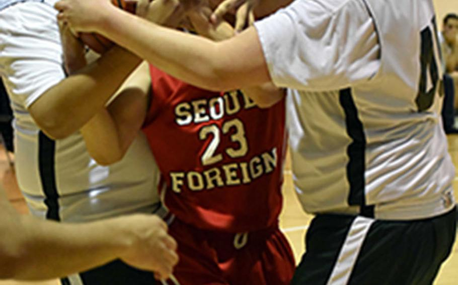Daegu's Elijah Bembischew and Jack Zimmer corral Seoul Foreign's Justin Chung and the ball during Friday's Korea boys basketball game, won by the Crusaders 59-43.