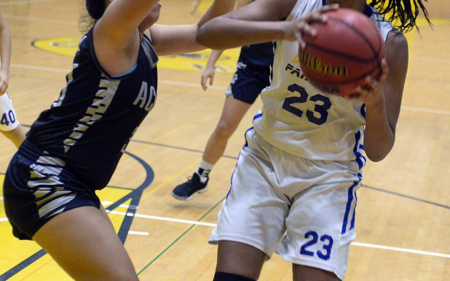 Yokota's Britney Bailey looks for room against Academy of Our Lady of Guam's Mika Dela Cruz during Friday's girls pool-play game in the 2nd American School In Japan Kanto Classic Basketball Tournament. The Panthers routed the Cougars 47-16.
