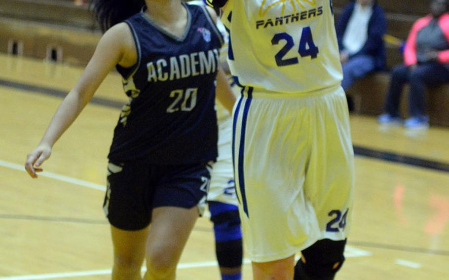 Yokota's Jordyn Logue drives for a layup ahead of Academy of Our Lady of Guam's Emilee Yamamoto during Friday's girls pool-play game in the 2nd American School In Japan Kanto Classic Basketball Tournament. The Panthers routed the Cougars 47-16.