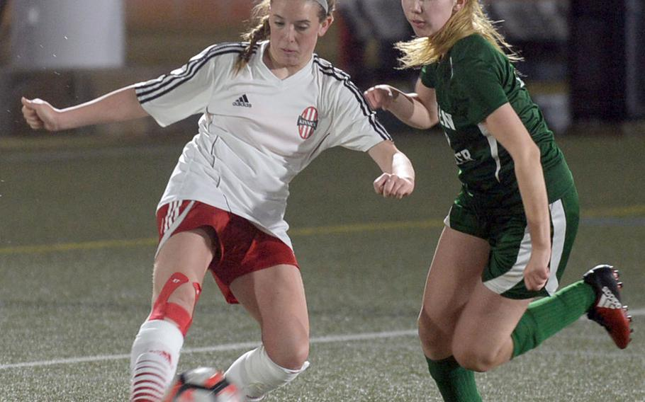 Nile C. Kinnick's Maggie Connelly boots a cross pass past Robert D. Edgren's Amber Aldridge during Friday's DODEA-Japan girls soccer match. The Red Devils clipped the Eagles 7-1.