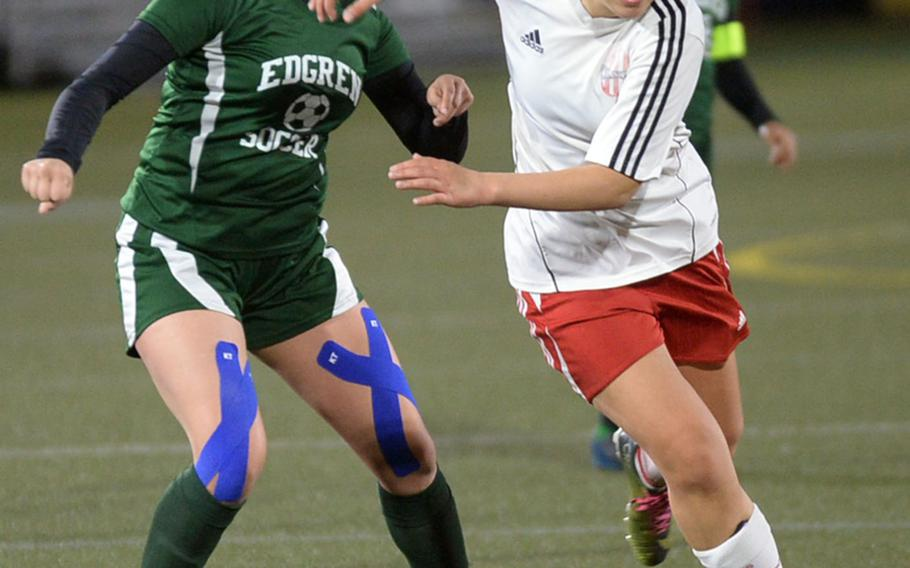 Nile C. Kinnick's Riassa Guenther dribbles past Robert D. Edgren's Kayla Ashby during Friday's DODEA-Japan girls soccer match. The Red Devils clipped the Eagles 7-1.