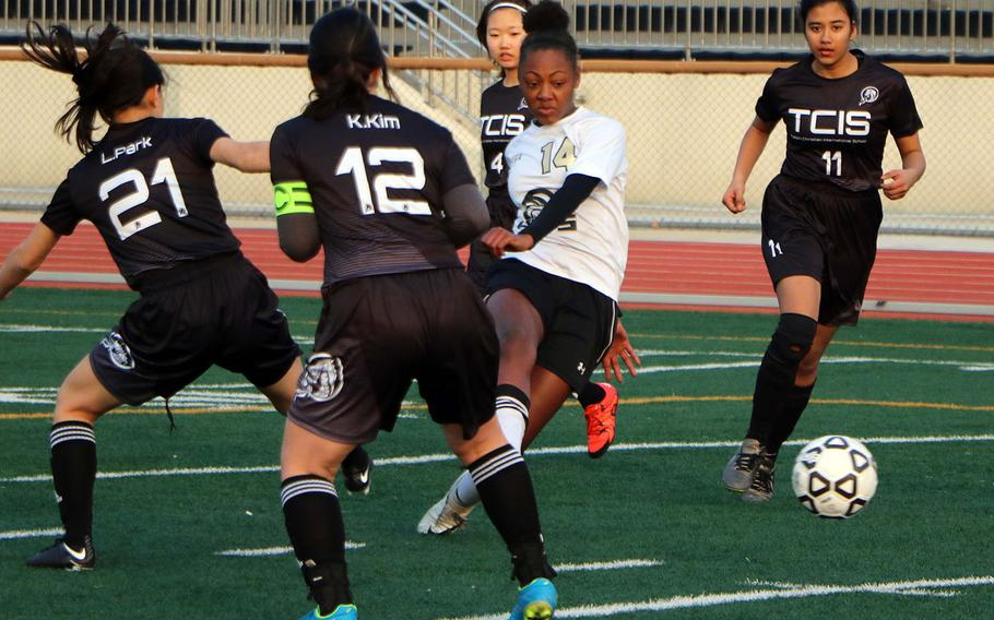 Humphreys' Hayden McMillan boots the ball through a gaggle of Taejon Christian defenders during Friday's Korea Blue girls soccer match. The Blackhawks won 5-1, continuing the team's best start in school history at 2-0-1.