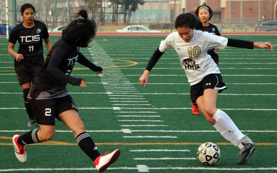 Humphreys' Ariel Stickar weaves her way between Taejon Christian defenders during Friday's Korea Blue girls soccer match. The Blackhawks won 5-1, continuing the team's best start in school history at 2-0-1.