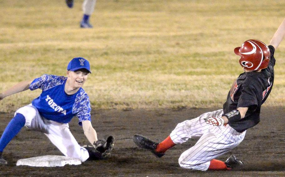Nile C. Kinnick's Terrence Berg is about to be put out at second base as Yokota's Jeff Mullarkey gets set to apply the tag during the Red Devils' 9-2 victory in Tuesday's Kanto Plain baseball game.