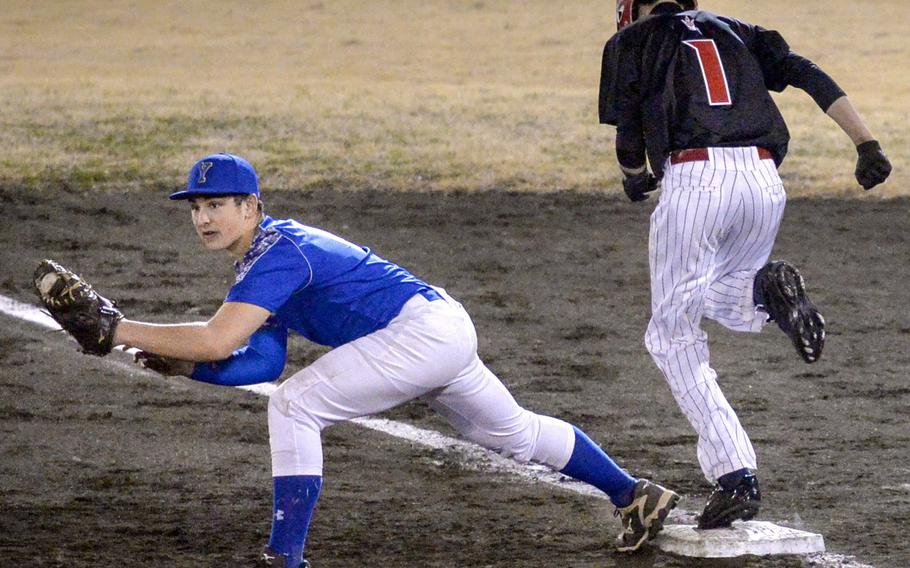 Nile C. Kinnick baserunner Kai Smith is out at first base as Yokota's Sean Caffrey stretches for the throw during the Red Devils' 9-2 victory in Tuesday's Kanto Plain baseball game.