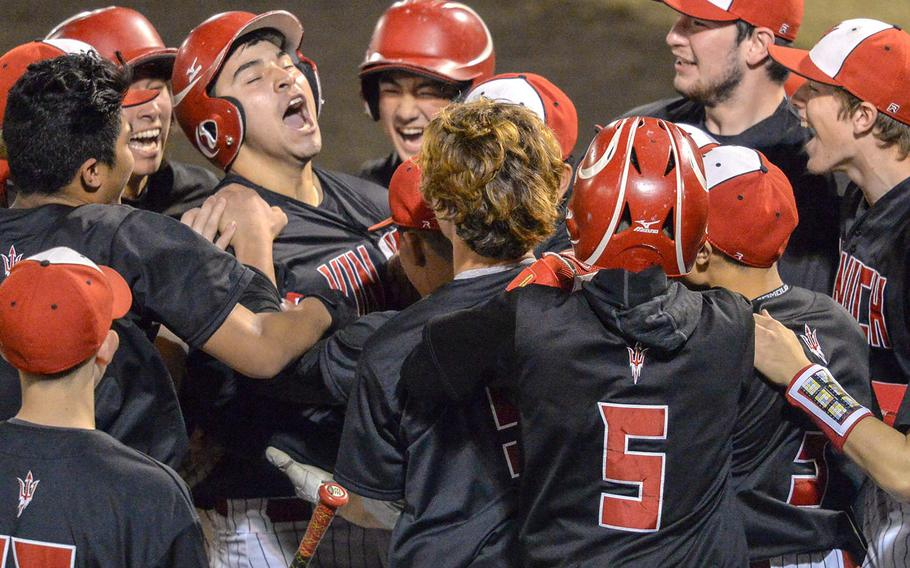 Nile C. Kinnick's Jonathan Acosta, third from left, and his teammates celebrate his home run against Yokota during the Red Devils' 9-2 victory in Tuesday's Kanto Plain baseball game.