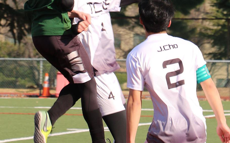 Daegu's David Spavins goes up to head the ball against Taejon Christian's Yisoo Han as Dragons teammate Hyunjoon Cho watches during Saturday's Korea Blue boys soccer match, won by the Dragons 1-0 on an own goal.