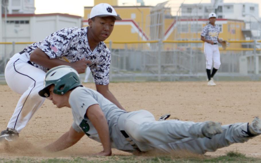 Kadena's Darious Hartwell applies the tag on Kubasaki's Jon Palmer during Wednesday's Okinawa baseball game, won by the Panthers 11-4.