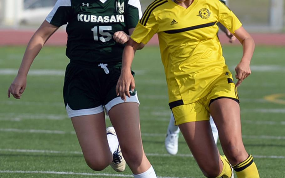 Kubasaki's Hanna Ervasti and Kadena's Adrianna Gomez chase the ball during Saturday's Okinawa girls soccer match. The Panthers won 3-0.