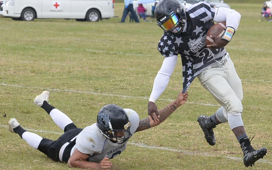 Hansen Outlaws' running back Aaron Walker tries to evade Okinawa Dragons defender Isaac Young during Saturday's USFJ-AFL game, won by the Outlaws 14-12.