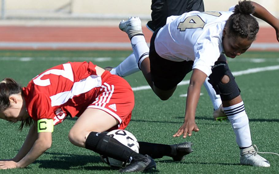 Seoul Foreign's Michelle Yun and Humphreys' Hayden McMillan tumble over the ball during Wednesday's Korea Blue girls soccer match, won by the Crusaders 2-1.