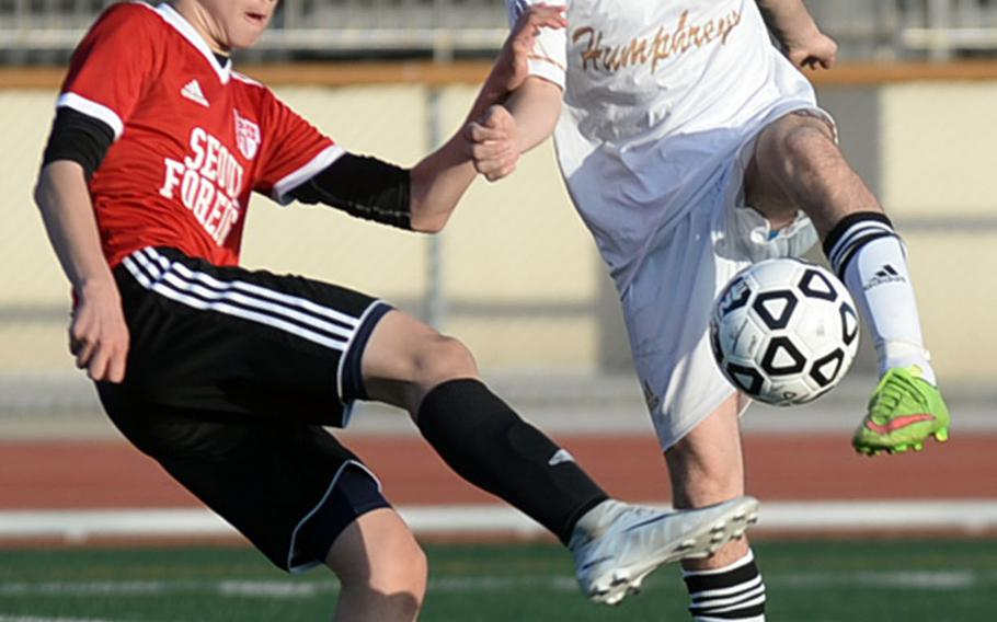 Seoul Foreign's Scott McLaughlin and Humphreys' Myles Rickett try to field the ball during Wednesday's Korea Blue boys soccer match, won by the Crusaders 9-2.