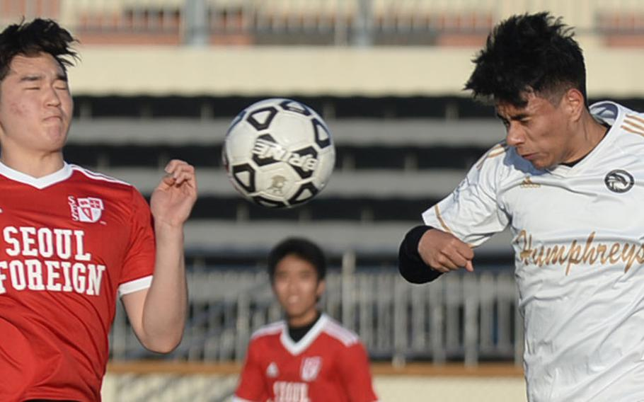 Seoul Foreign's Mark Ku and Humphreys' Christian Saaveda go up to head the ball during Wednesday's Korea Blue boys soccer match, won by the Crusaders 9-2.