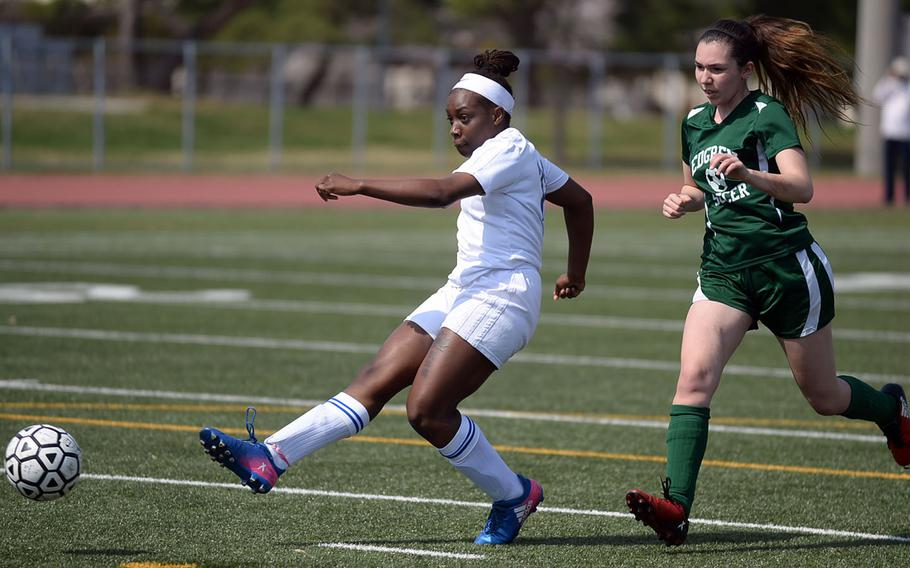 Yokota's Jamia Bailey fires a shot in front of Robert D. Edgren's Amber Eldridge during Saturday's DODEA-Japan girls soccer match, won by the Panthers 8-0.