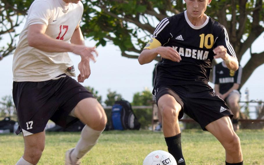 Okinawa Christian's Mark Lueder and Kadena's Kian Smith scuffle for the ball during Monday's boys soccer match, won by the Panthers 4-0.