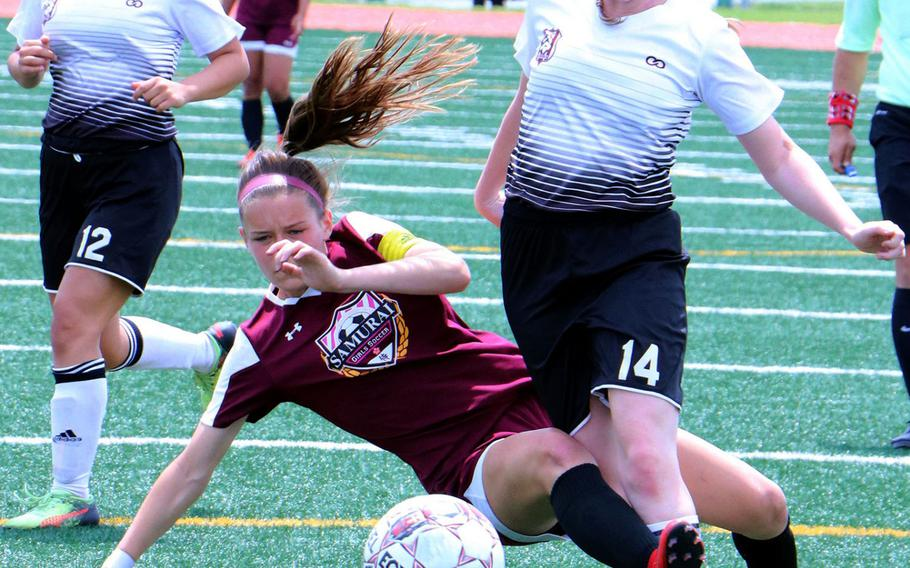 Zama's Abby Logan and Matthew C. Perry's Micayla Feltner get their legs tangled during Monday's pool-play match in the Far East Division II Soccer Tournament. The Samurai edged the Trojans 3-1.