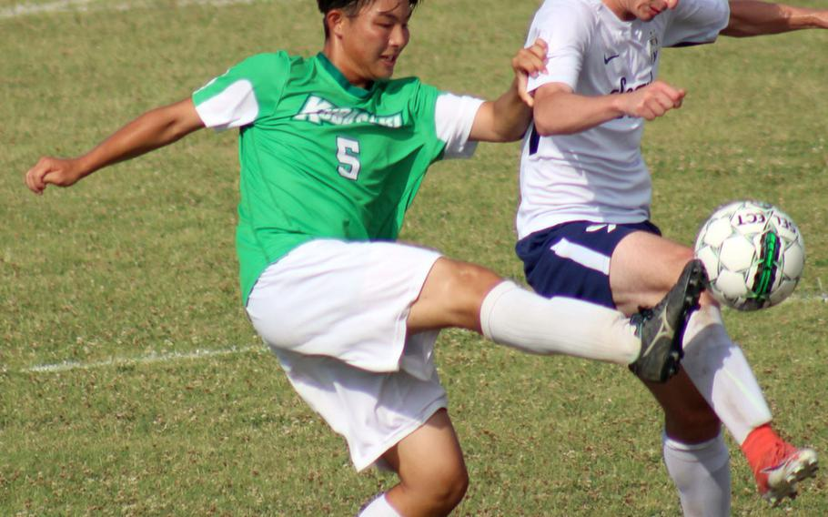 Kubasaki's Kaisei Taylor boots the ball past Seoul American's Jeff Hindman during Monday's round-robin match in the Far East Division I boys soccer tournament. The Dragons won 5-0.