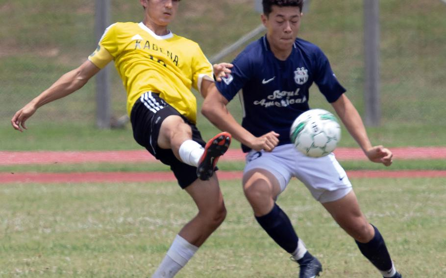 Kadena's Kian Smith and Seoul American's Ben Nagy scuffle for the ball during Monday's round-robin match in the Far East Division I boys soccer tournament. The Panthers won 1-0.