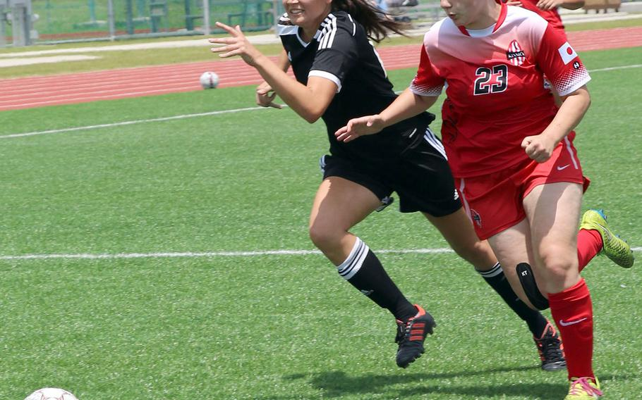 Kadena's Phoebe Bills and Nile C. Kinnick's Sydney Correll chase the ball during Monday's round-robin match in the Far East Division I soccerr tournament. Kinnick handed Kadena its first loss of the season 2-1.