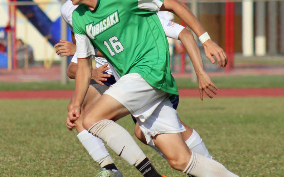 Kubasaki's Judge Morgan drives up field against Seoul American's defense during Monday's round-robin match in the Far East Division I boys soccer tournament. The Dragons won 5-0.