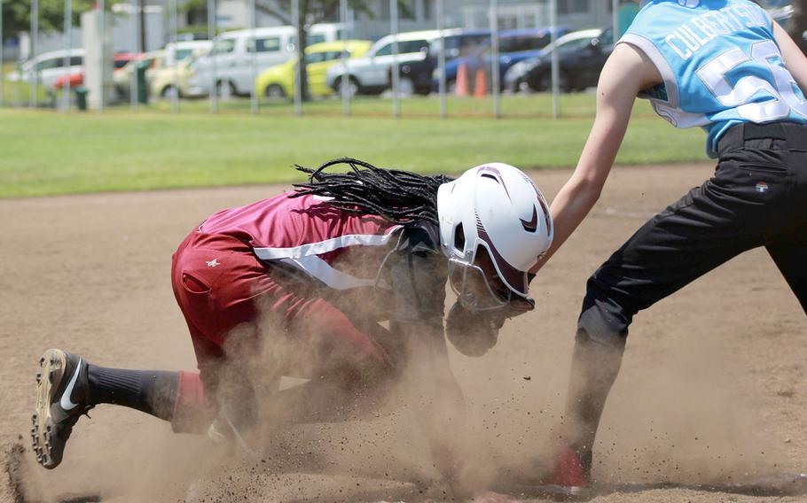 Perry's Valarie Thomas dives back to the bag ahead of the tag by Osan's Chloe Culbertson during Tuesday's knockout-round game in the Far East Division II softball tournament. The Samurai won 12-3.