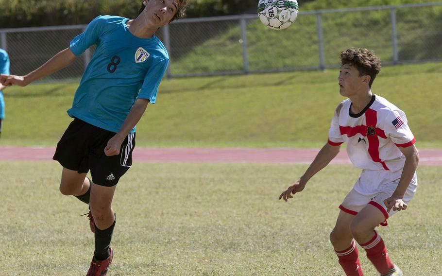 Kadena's Eric Fletcher heads the ball in Nile C. Kinnick's Cael Bowen's direction during Tuesday's semifinal match in the Far East Division I boys soccer tournament. The Panthers won 2-1 in extra time.