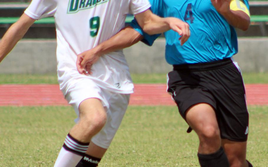 Kubasaki's Jack Boran and Kadena's Quentin Moore scuffle for the ball during Tuesday's round-robin match in the Far East Division I boys soccer tournament. The Dragons blanked the Panthers 3-0.