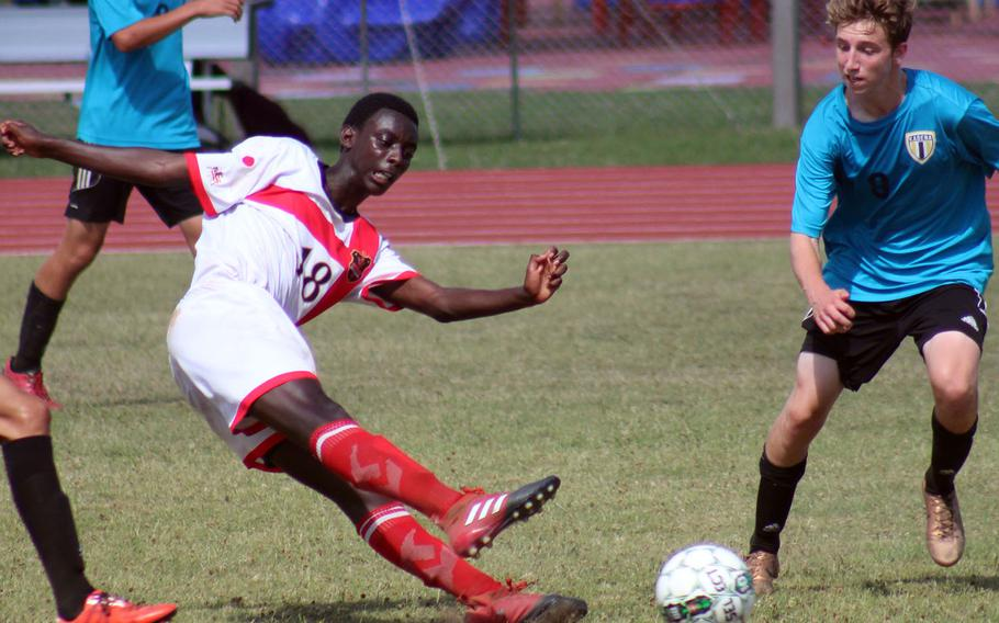 Nile C. Kinnick's Akimanzi Siibo boots the ball past Kadena's Brennan Slinger during Tuesday's semifinal match in the Far East Division I boys soccer tournament. The Panthers won 2-1 in overtime.