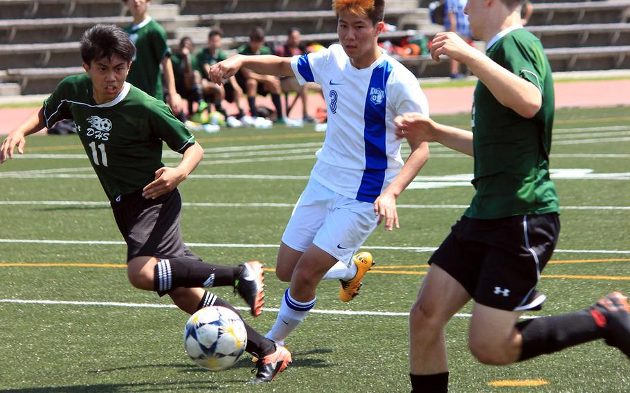Christian Academy Japan's SeongJoon Park dribbles between Daegu defenders during Tuesday's playoff game in the Far East Division II boys soccer tournament. The Knights won 6-1.