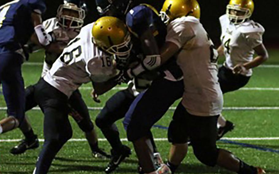 Guam High running back Sincere Powell gets sandwiched by two Tiyan defenders.