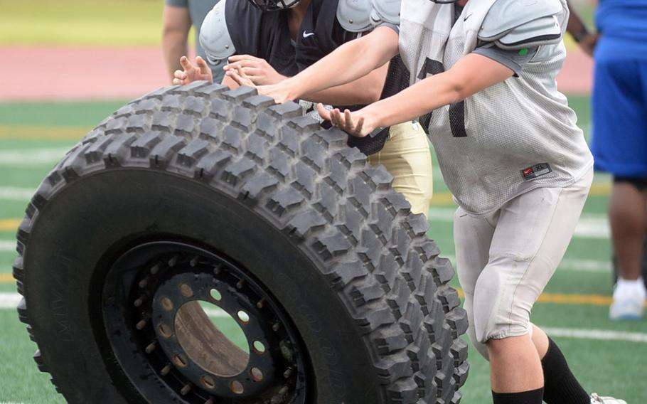 Blackhawks linemen Lucas Gengler and Chris Hampton shove over their quarry during a heavy tire drill designed to build strength.