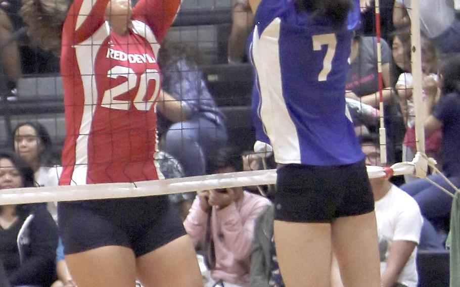 Nile C. Kinnick's Madelyn Gallo and Christian Academy Japan's Keziah Sou battle at the net for the ball during the Knights' five-set win Tuesday over the Red Devils.