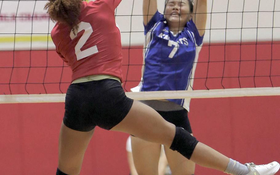 Christian Academy Japan's Keziah Sou tries to block a spike by Nile C. Kinnick's Sontti Sesay during the Knights' five-set win Tuesday over the Red Devils.