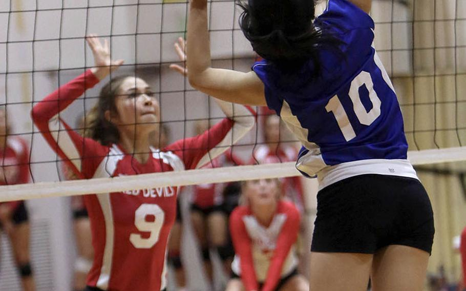 Christian Academy Japan's Mariko Maeda prepares to spike against Nile C. Kinnick's Melissa Rose during the Knights' five-set win Tuesday over the Red Devils.