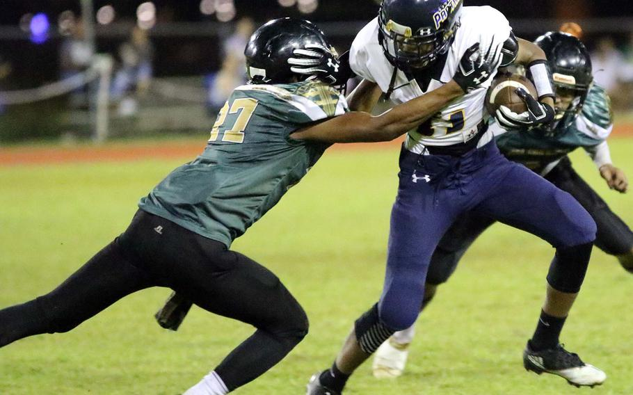 Guam High's Elijah Ferrell-Ayers tries to avoid the tackle of John F. Kennedy's Jacobe Quinata.