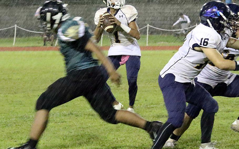 Guam High quarterback Travon Jacobs looks to throw in a driving rain at John F. Kennedy's Ramsey Field.