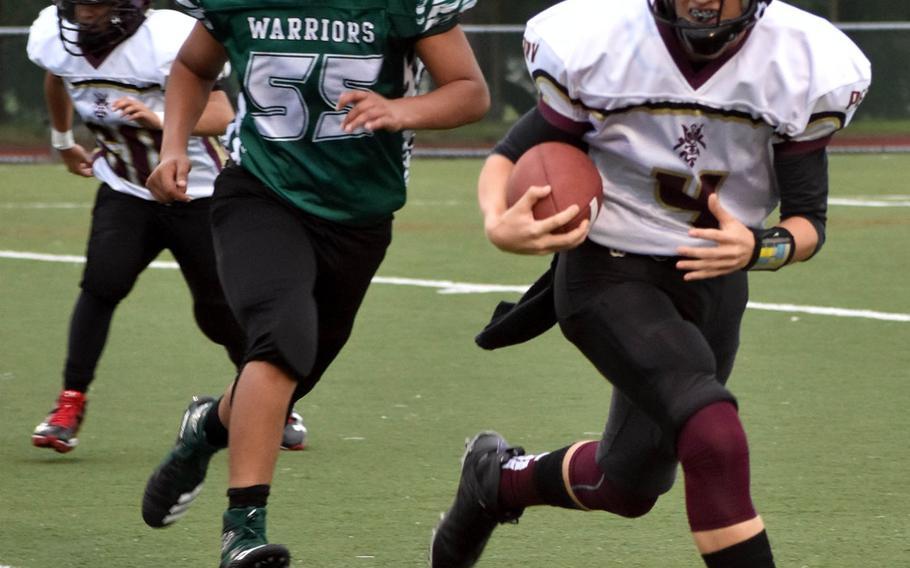 Matthew C. Perry quarterback Jackson Ramp tries to avoid the tackle of Daegu's Rodrigo Roque-Aquino.