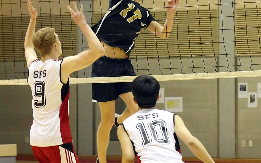 Humphreys' Connor Coyne skies for the ball against Seoul Foreign's Matt Daly and Josh Ko during Wednesday's three-set victory by the Crusaders over the Blackhawks.
