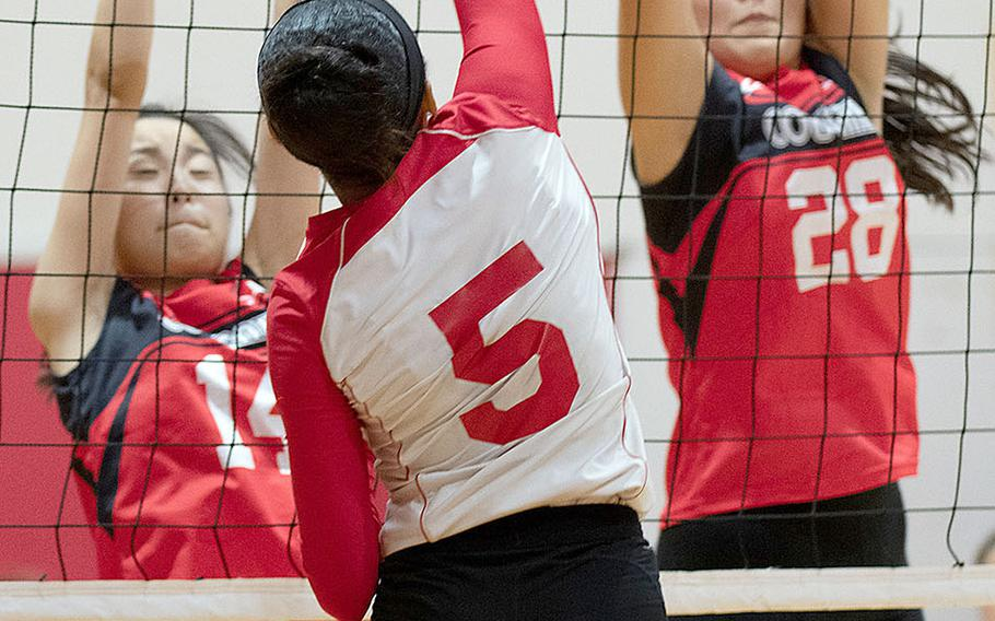 Nile C. Kinnick's Lynelle Adepoju tries to hit through the double block of Emi Ishikawa and Yoko Hara of St. Maur during Wednesday's three-set victory by the Red Devils over the Cougars.