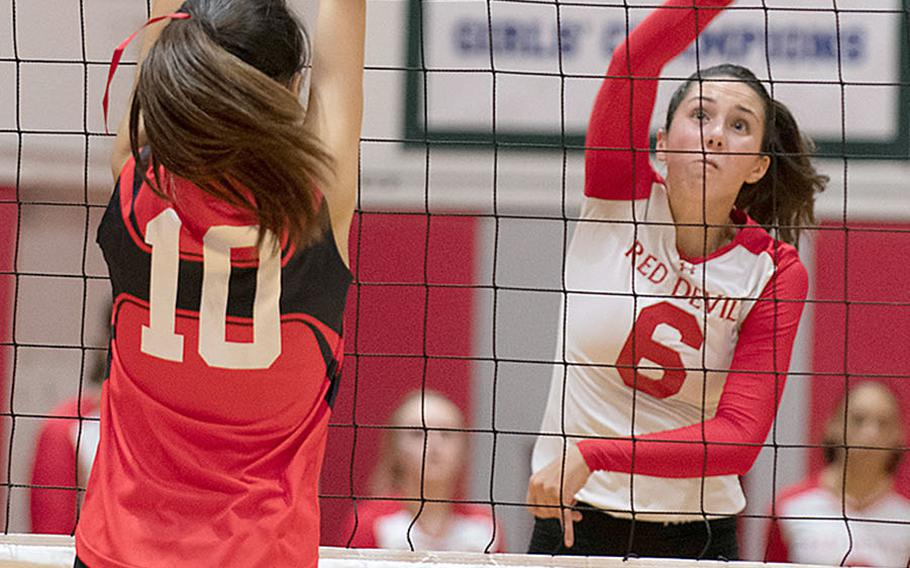 Nile C. Kinnick's Emma Stevens hits the ball past St. Maur's Rei Ozawa during Wednesday's three-set victory by the Red Devils over the Cougars.