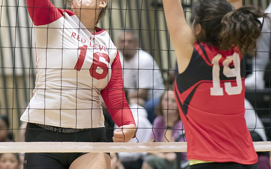 Nile C. Kinnick's Madelyn Gallo tries to hit past St. Maur's Sophia Baker during Wednesday's three-set victory by the Red Devils over the Cougars.