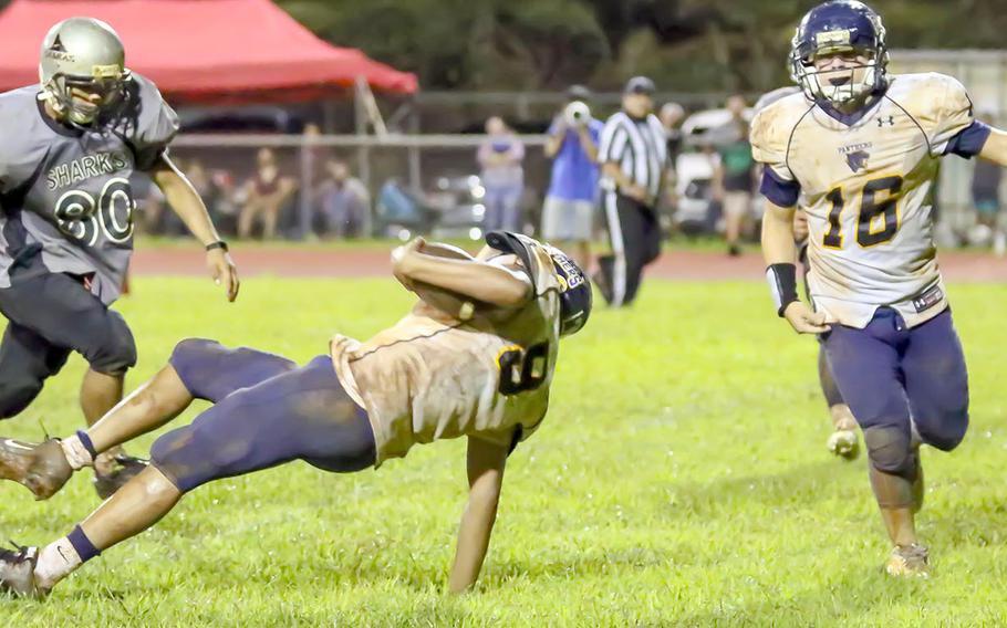 Guam High quarterback RaSean Jacobs tumbles into the end zone between teammate Drew Mestas and Simon Sanchez's Dylan Cabe.