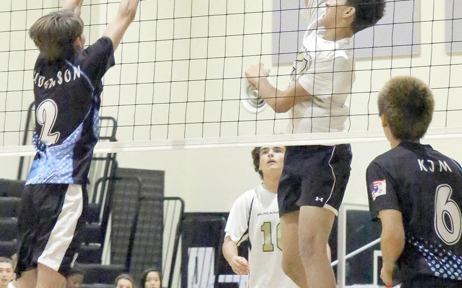 Humphreys' Collin Metcalf goes up to hit against Osan's Jaxon Andersson and Minsung Kim in Friday's four-set win by the Cougars over the Blackhawks.