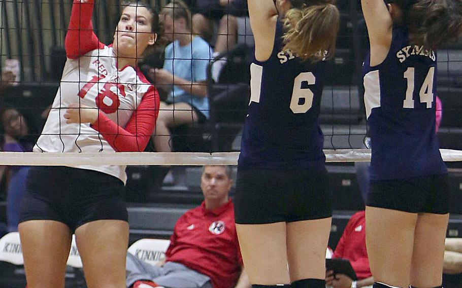 Nile C. Kinnick's Madelyn Gallo smacks a spike past Sacred Heart's Noe Shimojo and Maya Festenhausen during Thursday's three-set win by the Red Devils over the Symbas.