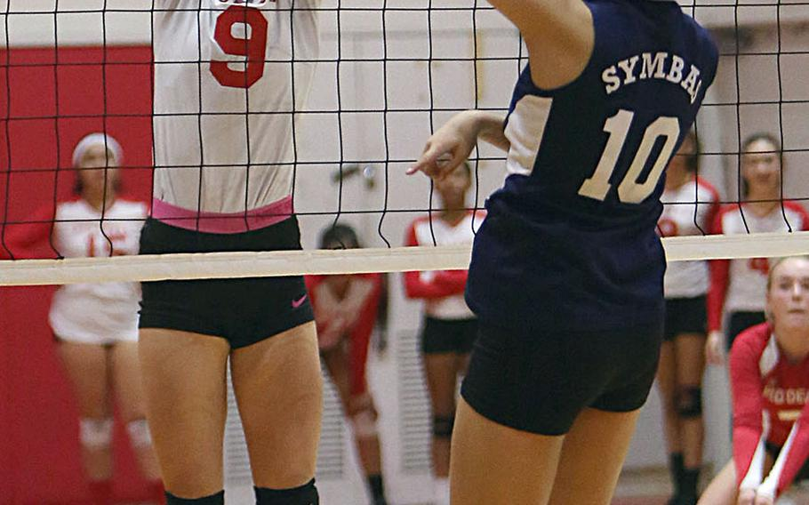 Nile C. Kinnick's Melissa Rose blocks a shot by Sacred Heart's Karin Kosugi -- one of three blocks by Rose during Thursday's three-set win by the Red Devils over the Symbas.