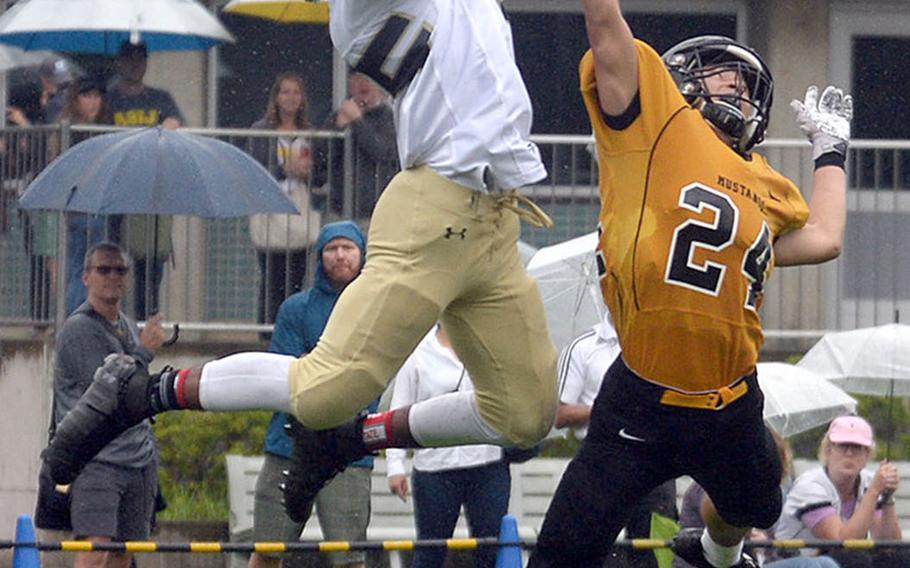 Humphreys' Junior Gregory leaps for a touchdown catch over American School In Japan defender Tei Laughlin.
