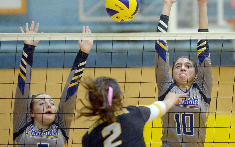American School In Japan's Aloha Suto slams a spike between the block of Yokota's Madison Eaton and Adrianna Diaz during Thursday's three-set win by the Mustangs.