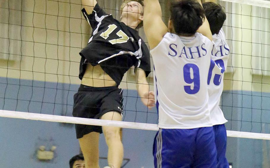 Humphreys' Connor Coyne skies for a spike against Brian Choe and Timothy Stewart of Seoul American during Wednesday's three-set win by the Blackhawks over the Falcons.